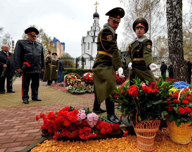 Honour guard soldiers lay flowers at the Chernobyl victims' memorial in Minsk on April 26, 2016. The world marks 30 years since the world's worst nuclear accident at Chernobyl killed thousands and forced a global rethink about the wisdom of relying on atomic fuel. (Photo by Maxim Malinovsky/AFP Photo)