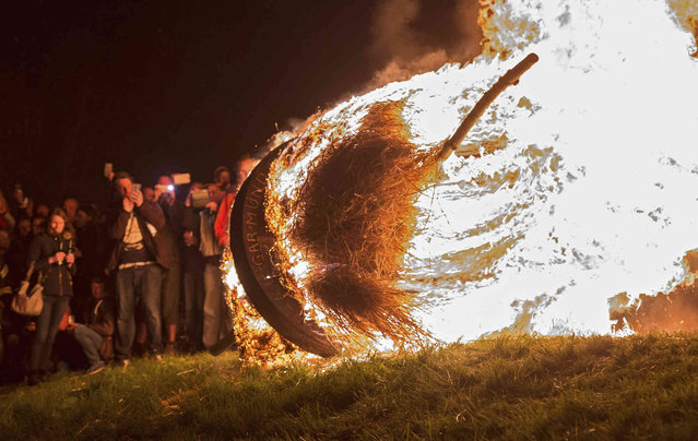 Spectators watch a burning wheel during an old easter tradition in Luegde, Germany, Saturday, April 21, 2019. (Photo by Caroline Seidel/dpa via AP Photo)