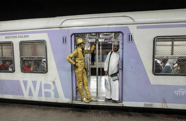 Girjesh Kumar Gaud, 22, an aspiring Bollywood actor who works as a performance artist, stands on the doorway of suburban train as he travels back home in Mumbai, India, July 16, 2019. (Photo by Prashant Waydande/Reuters)