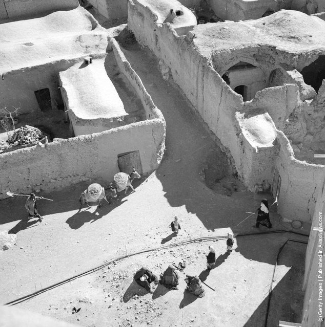 1962: A view of a village consisting of mud buildings near Isfahan in Iran. At  the crossroads a group of women can be seen winding cotton onto reels and in the distance a man guides two heavily-laden donkeys