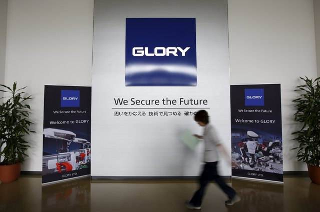 An employee walks past at the entrance of a factory of Glory Ltd., a manufacturer of automatic change dispensers, in Kazo, north of Tokyo, Japan, July 1, 2015. (Photo by Issei Kato/Reuters)