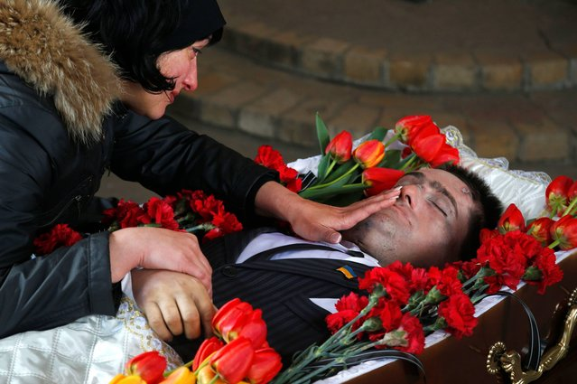 Elena, the widow of slain council man Volodymr Rybak caresses the face of her husband as his body lays in the coffin prior to his funeral after his body was found on Tuesday after his alleged abduction by pro-Russian insurgents in the eastern city of Horlivka, Ukraine, Thursday, April 24, 2014. (Photo by Sergei Grits/AP Photo)
