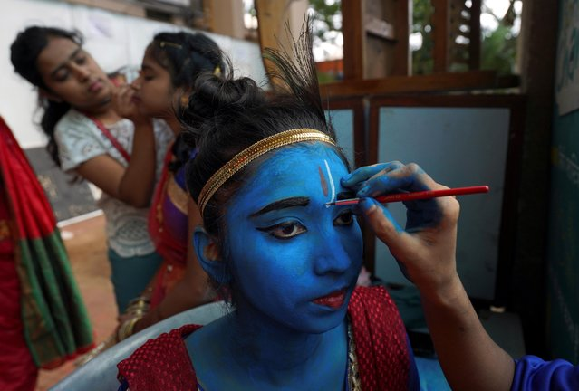 A student has her face painted before taking part in a cultural event to mark the Hindu festival of Janmashtami, or the birth anniversary of Hindu Lord Krishna, inside a college in Mumbai, August 21, 2019. (Photo by Hemanshi Kamani/Reuters)