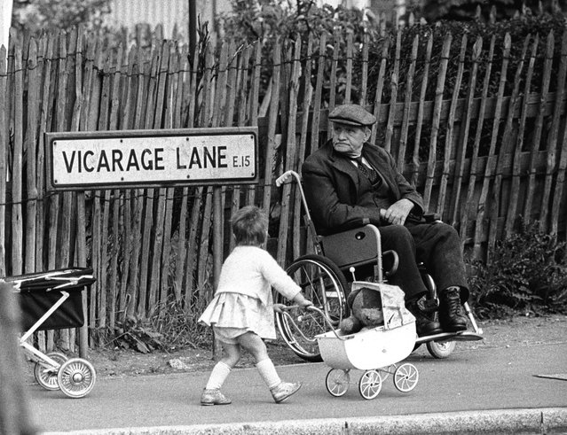 A little girl pushes her teddy bear past a wheelchair-bound gentleman on Vicarage Lane, in the East End of London, 1960s. (Photo by Steve Lewis/Getty Images)