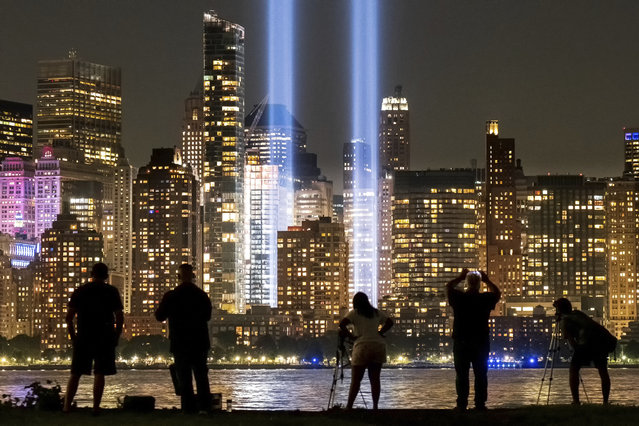 Spectators and photographers look across the Hudson River from Jersey City, N.J., at the Sept. 11 tribute lights in New York City on the 18th anniversary, Wednesday, September 11, 2019, of the attacks on the twin towers of the World Trade Center. (Photo by J. David Ake/AP Photo)