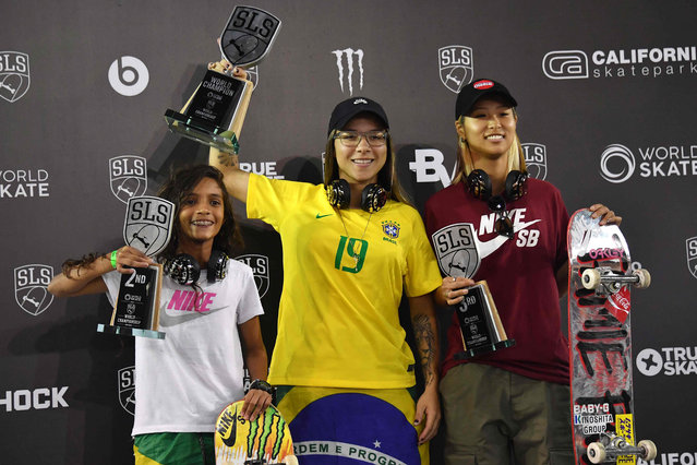 Brazilian skateboarder Pamela Rosa (C) celebrates with Brazilian Rayssa Leal (L) and Japanese Aori Nishimura (R), after getting the fist, second and third places respectively in the Street League Skateboarding world championship in Sao Paulo on September 22, 2019. The championship qualifies for the Tokyo 2020 Olympics where Skateboarding will feature for the first time as an event. (Photo by Nelson Almeida/AFP Photo)