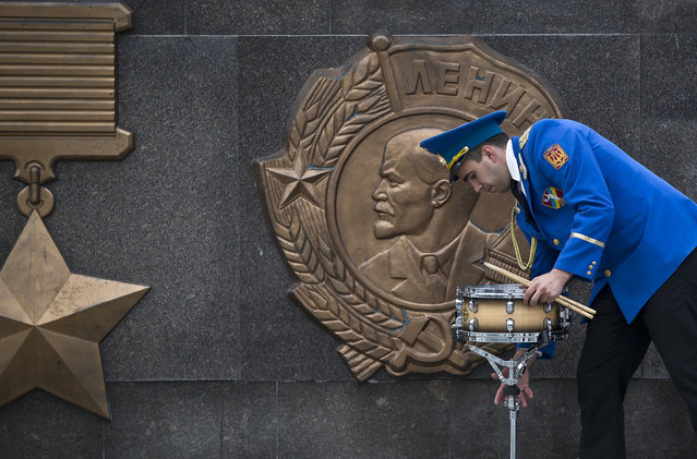A member of a military band handles a drum, backdropped by a depiction of Soviet revolutionary leader Vladimir Lenin, before Victory Day celebrations in Odessa, Ukraine, Friday, May 9, 2014. (Photo by Vadim Ghirda/AP Photo)