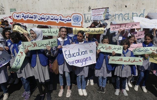 Palestinian pupils hold placards during a rally in support of the United Nations organisation for Palestinian refugees (URRWA) in front of their headquarters in Gaza City on September 17, 2019. The United States last year cut off its roughly $300 million annual donation to UNRWA, which provides education, health and other key services for the Palestinian refugees with funding from international donors. (Photo by Mahmud Hams/AFP Photo)