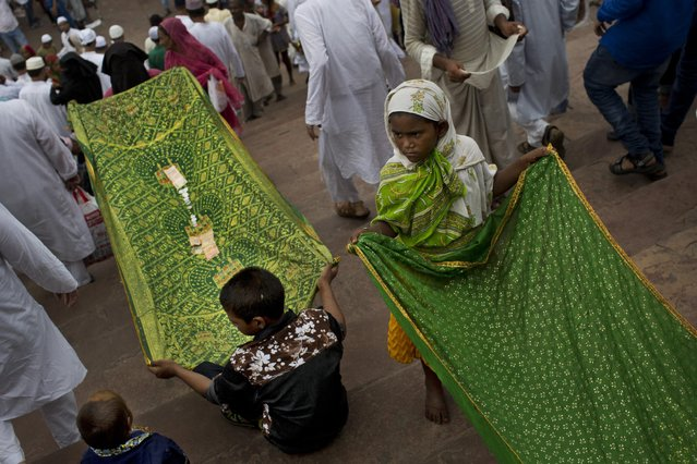 Indian children beg for alms outside the Jama Masjid mosque during the holiday of Eid al-Fitr in New Delhi, India, Saturday, July 18, 2015. (Photo by Bernat Armangue/AP Photo)