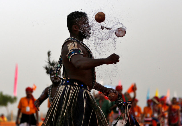 A performer breaks a coconut with his head during a ceremony to celebrate Gujarat Foundation Day in Ahmedabad, India, May 1, 2017. (Photo by Amit Dave/Reuters)