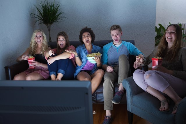 A group of young people laughing and watching a funny humorous show together on TV. (Photo by Yin Yang/Getty Images)