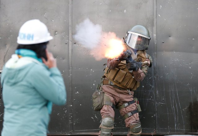 A riot police officer fires tear gas during a protest against Chile's government in Valparaiso, Chile on November 4, 2019. (Photo by Rodrigo Garrido/Reuters)