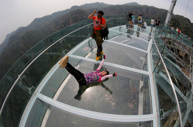 Visitors take pictures as they pose on the glass sightseeing platform on Shilin Gorge in Beijing, China, May 27, 2016. (Photo by Kim Kyung-Hoon/Reuters)
