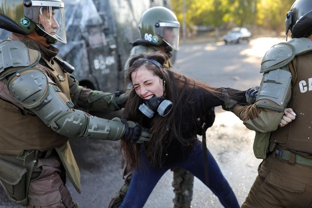 A demonstrator reacts as she is detained by riot policemen during a protest against Chile's government in Santiago, Chile, November 30, 2019. (Photo by Pablo Sanhueza/Reuters)