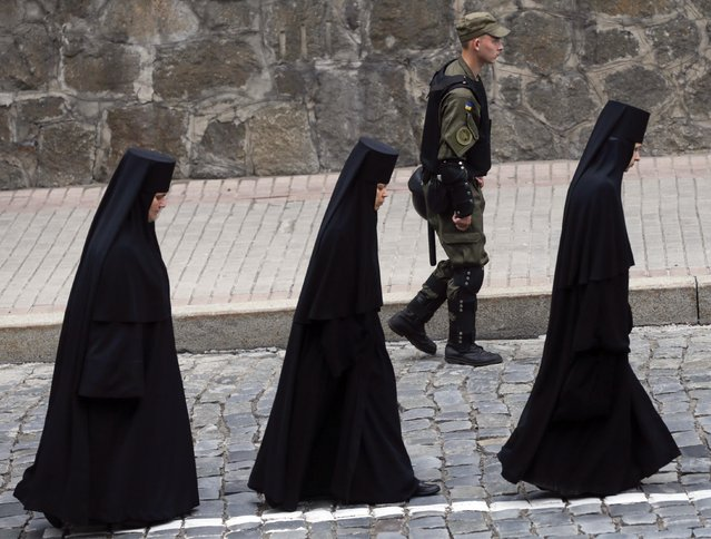A member of the National Guard walks next to nuns during a procession marking the 1,000th anniversary of the death of Vladimir the Great in Kiev, Ukraine, July 27, 2015. Ukrainians mark on July 28 the Christianisation of the country, which was known as Kievan Rus' at the time, by its grand prince, Vladimir I (Vladimir the Great), in 988 AD. (Photo by Valentyn Ogirenko/Reuters)