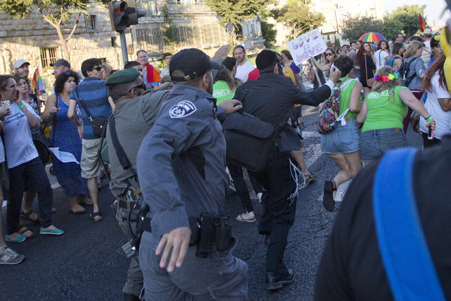 Security forces reach for a knife-wielding ultra-Orthodox Jew attacking people with a knife during a Gay Pride parade Thursday, July 30, 2015 in central Jerusalem. (Photo by Sebastian Scheiner/AP Photo)