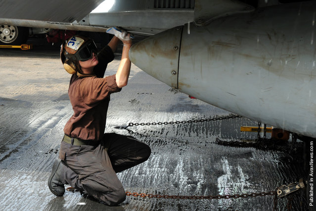 Aviation Structural Mechanic Airman Ashley Botbyl, from Warwick, N.Y., scrubs down an F/A-18C Hornet assigned to the Blue Diamonds of Strike Fighter Squadron (VFA) 146 aboard the aircraft carrier USS Ronald Reagan (CVN 76)