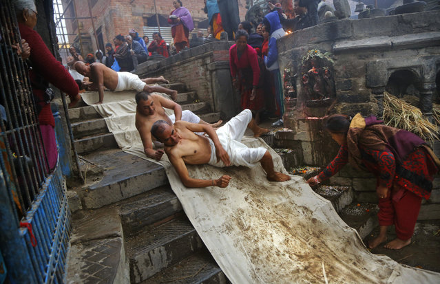 In this Thursday, January 24, 2019, file photo, Nepalese Hindu devotees roll on the ground as part of a ritual during the Madhav Narayan festival in Bhaktapur, Nepal. During this festival, devotees recite holy scriptures dedicated to Hindu goddess Swasthani and Lord Shiva. Unmarried women pray for a good husband while those married pray for the longevity of their husbands by observing a month-long fast. (Photo by Niranjan Shrestha/AP Photo)