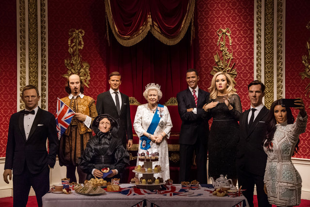 Wax figures of Britain's Queen Elizabeth II, centre, along with figures of Daniel Craig, from left, William Shakespeare, Madame Tussaud, David Beckham, Barack Obama, Adele, Benedict Cumbertach and Kim Kardashian are unveiled to celebrate the Queen's 90th birthday at Madame Tussauds, in London, Thursday, June 9, 2016. (Photo by Vianney Le Caer/Invision/AP Photo)