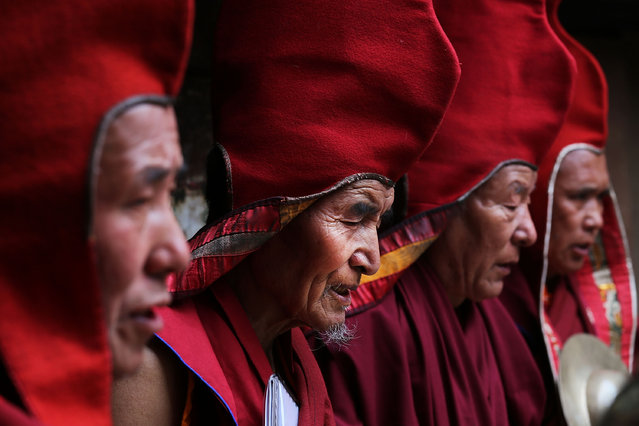 Buddhist monks pray while performing a ceremony in the former King's palace during the Tenchi Festival on May 25, 2014 in Lo Manthang, Nepal. The Tenchi Festival takes place annually in Lo Manthang, the capital of Upper Mustang and the former Tibetan Kingdom of Lo. Each spring, monks perform ceremonies, rites, and dances during the Tenchi Festival to dispel evils and demons from the former kingdom. (Photo by Taylor Weidman/Getty Images)