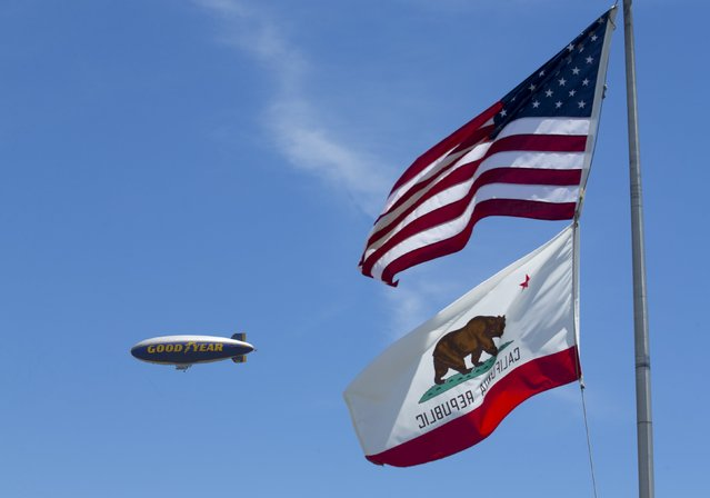 """The Goodyear blimp """"Spirit of America"""" flies past flags in Carson, California August 5, 2015. (Photo by Mike Blake/Reuters)"""