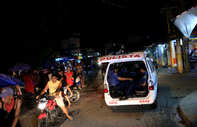 Members of the Philippine National Police drive past a checkpoint along a main street of Las Pinas city, south of Manila, Philippines June 10, 2016. (Photo by Romeo Ranoco/Reuters)