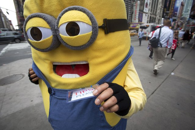 """A man dressed as a """"minion"""" from the """"Despicable Me"""" movies poses in Times Square in New York, on Jule 10, 2014. Because of concerns about some characters' aggressive behavior, New York's city council is writing a bill to regulate the costumed characters. (Photo by Carlo Allegri/Reuters)"""