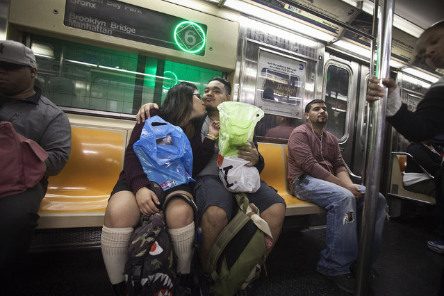 A couple kisses as they ride the 6 train in the Bronx borough of New York October 27, 2014. (Photo by Carlo Allegri/Reuters)