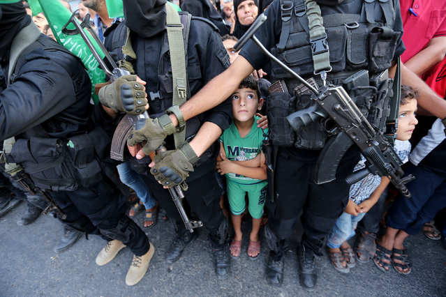 Palestinian boys stand next to Hamas militants as they take part in a military show against Israel's newly-installed security measures at the entrance to the al-Aqsa mosque compound, in Khan Younis, in the southern Gaza Strip on July 20, 2017. (Photo by Ibraheem Abu Mustafa/Reuters)