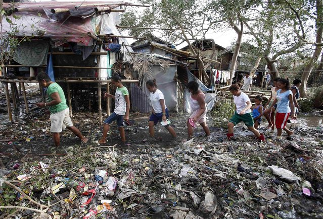 Residents walk amidst debris and mud brought by Typhoon Rammasun (locally named Glenda) in a coastal village of sea gypsies, also known as Badjaos, in Batangas city, south of Manila, July 17, 2014. The Philippines set to work clearing debris, reconnecting power and rebuilding flattened houses on Thursday after the typhoon swept across the country killing 38 people, with at least eight missing, rescue officials said. (Photo by Erik De Castro/Reuters)