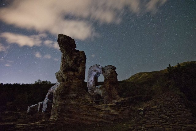 A long exposure image showing a Perseids meteor (L) streaking across the night sky over the remains of St. Ilia Roman early Christian basilica dated back to the 5th6th century AD near the town of Pirdop, early on August 12, 2015. (Photo by Nikolay Doychinov/AFP Photo)