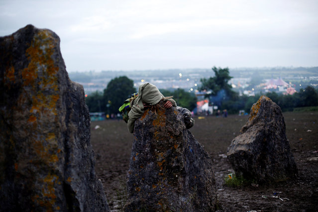 A reveller sleeps on a stone at Worthy Farm in Somerset during the Glastonbury Festival, Britain June 23, 2016. (Photo by Stoyan Nenov/Reuters)