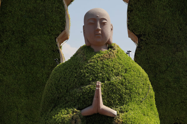 "A sculpture of Monk Tang (also known as Tang Xuanzang in Chinese noval ""Journey to the West"") wearing a ""green coat"" made up of green plants was seen on at Dayanta July 15, 2014 in Xi'an, Shaanxi province of China. A hot weather with the temperature of 35 degree celsius hit Xi'an on July 15. (Photo by ChinaFotoPress/Getty Images)"