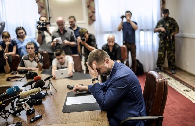 "Self-proclaimed Prime Minister of the pro-Russian separatist ""Donetsk People's Republic"" Alexander Borodai (C) gestures as he gives a press-conference in the eastern Ukrainian city of Donetsk, on July 19, 2014. Borodai ruled out on July 18, 2014 a temporary truce with government forces but pledged to allow investigators to access the site of downed Malaysia Airlines jet MH17. (Photo by Bulent Kilic/AFP Photo)"