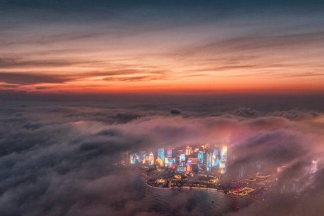 "In this April 20, 2018, file aerial photo released by China's Xinhua News Agency, advection fog drifts across skyscrapers on the waterfront in Qingdao in eastern China's Shandong Province. Chinese leaders have long been sensitive about their communist country's international image. Now, they are battling back, investing in diplomacy and a courtship of hearts and minds, just as the United States digs in on the Trump administration's ""America First"" mindset. (Photo by Lu Hui/Xinhua via AP Photo/File)"
