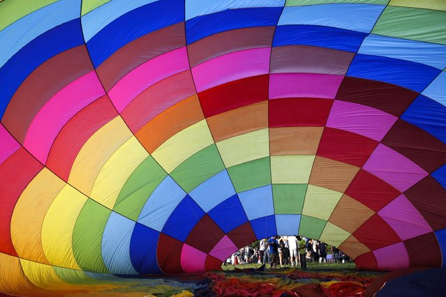 Ground staff inflates a hot air balloon during the 2016 International Hot Air Balloon Festival in Taitung, southeast of Taiwan, 01 July 2016. (Photo by Ritchie B. Tongo/EPA)