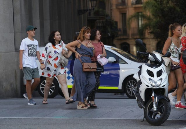 People move away from the area after a van plowed into the crowd, injuring several people in Barcelona, Spain on August 17, 2017. (Photo by Albert Llop/Anadolu Agency/Getty Images)
