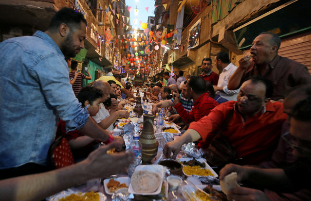 Residents of Ezbet Hamada in Cairo's Mataria district gather to eat Iftar, the meal to end their fast at sunset, during the holy fasting month of Ramadan in Cairo, Egypt, May 20, 2019. (Photo by Mohamed Abd El Ghany/Reuters)