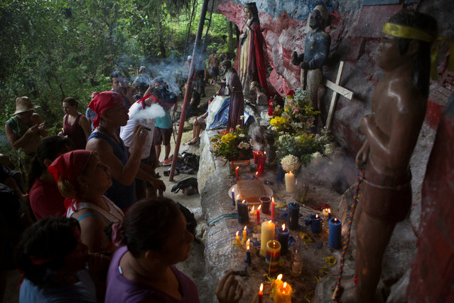 People pray, smoke cigars and light up candles at the Maria Lionza shrine at the Sorte Mountain on the outskirts of Chivacoa, in the state of Yaracuy, Venezuela October 11, 2015. (Photo by Marco Bello/Reuters)