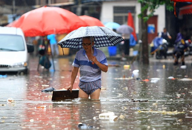 A man makes his way through a flooded area in Changsha, central China's Hunan province, on July 15, 2014. The meteorological department in Hunan issued an orange alert for storm, as heavy rain hits the province's central and northern area, local media reported. (Photo by AFP Photo/Stringer)