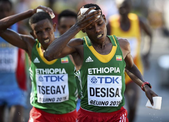 Yemane Tsegay of Ethiopia (L) and Lelisa Desisa of Ethiopia (R) wipes off their perspiration during the men's marathon at the 15th IAAF World Championships at the National Stadium in Beijing, China August 22, 2015. (Photo by Dylan Martinez/Reuters)