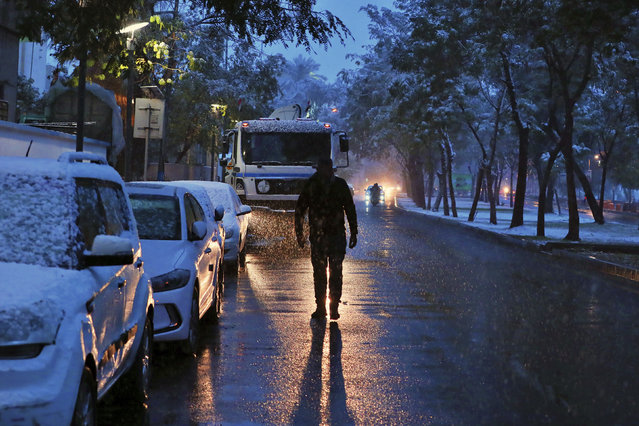 A man walks on a road while it snows in Baghdad, Iraq, Tuesday, February 11, 2020. (Photo by Hadi Mizban/AP Photo)