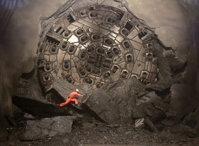 A miner climbs on excavated rocks after a giant drill machine broke through at the final section Sedrun-Faido, at the construction site of the NEAT Gotthard Base Tunnel March 23, 2011. (Photo by Arnd Wiegmann/Reuters)