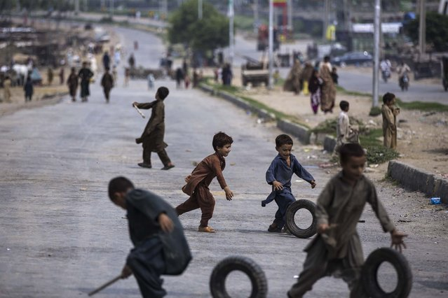 Children play with tyres in a main road which is empty of traffic, after being blocked by the Pakistani police with shipping containers, on the outskirts of Islamabad, Pakistan, Thursday, August 14, 2014. Roads leading to the Capital are being blocked in run up to announced protests by cricketer-turned-politician Imran Khan and anti-government cleric Tahir-ul-Qadri. Both men want the government to step down and new elections to be held. (Photo by Muhammed Muheisen/AP Photo)