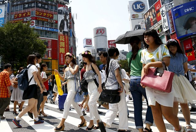 People cross a junction in front of advertising billboards in the Shibuya shopping district in Tokyo July 31, 2015. Core consumer prices in Tokyo fell 0.1 percent in the year to July, government data showed on Friday, marking the first year-on-year decline since April 2013. (Photo by Thomas Peter/Reuters)