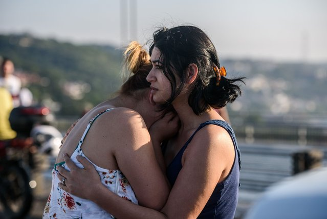 Women react after people took over military position on the Bosphorus bridge in Istanbul on July 16, 2016. The number of dead from a coup attempt in Turkey has risen to 90, the state-run news agency Anadolu reported on July 16, 2016, adding that 1,154 people were wounded. Nearly 200 unarmed soldiers at the Turkish military headquarters have meanwhile surrendered, an official said, adding that special troops were currently securing the complex. (Photo by Ozan Kose/AFP Photo)