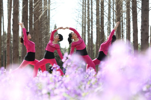 Women practise yoga amid blooming orchids in Xuyi, Jiangsu province, China on March 20, 2020. (Photo by Costfoto/Barcroft Media)