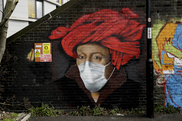 A mural by street artist Lionel Stanhope with a face mask reference to coronavirus painted on a bridge wall in Ladywell, south east London, Thursday, April 2, 2020. (Photo by Matt Dunham/AP Photo)