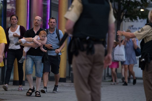 Police escort people that were in the mall during the shooting in Munich, Germany on July 22, 2016. Several people have been killed on Friday after an unknown number of assailants opened fire in a shopping mall in the southern German city of Munich. (Photo by Sebastian Widmann/Anadolu Agency/Getty Images)