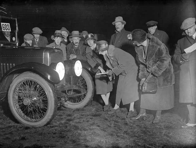 Motorists inspect a device designed to reduce dazzle from a vehicle's headlights. Here fitted on an Austin, 1925. (Photo by MacGrego)